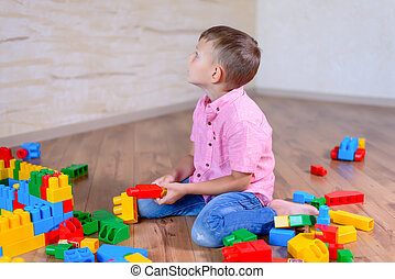Little boy playing with construction toy blocks