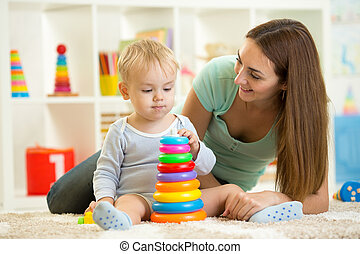 child and woman play together in nursery - child boy playing...
