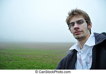 Young man with glasses in field