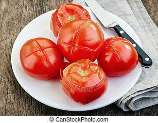 blanched tomatoes on plate, ready for peeling