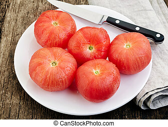 blanched tomatoes on white plate