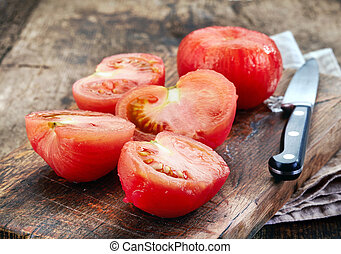 blanched tomatoes on wooden cutting board
