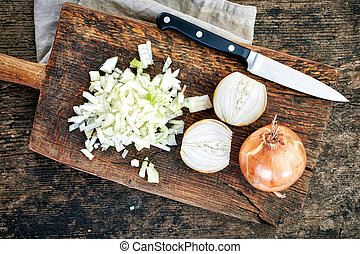 chopped onions on wooden cutting board, top view