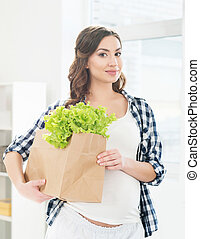 Beautiful woman with a shopping bag with lettuce.