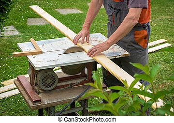Carpenter working with electric buzz saw cutting wooden...