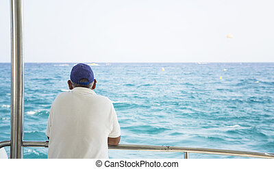 man on a boat looking at the sea alone
