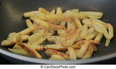 French fries are fried in a pan - Sprinkle seasoning the...
