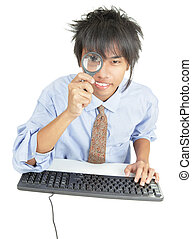 Young Asian businessman peering thru magnifier - Young Asian...