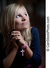 Beautiful young woman with a rosary/prayer beads praying to God