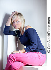portrait of a pretty young blonde woman listening to music on her mp3 player (daydreaming)