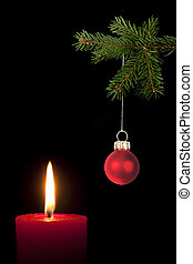 Fir branch with Christmas tree ball and red candle in front...