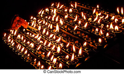 Woman lighting prayer candle in a church - Woman lighting...