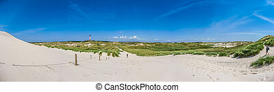 Beautiful dune landscape with traditional lighthouse at...
