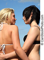 Two young women flirting at the beach
