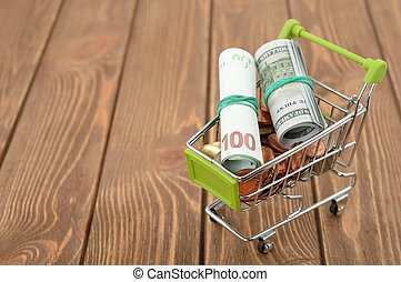 Shopping cart full of money, on a brown background