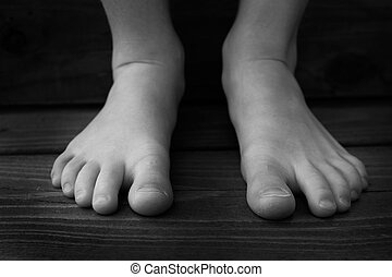 Bare Feet of Child Black and White on Wood Grain Steps