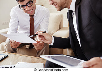 Explanation - Businessman pointing at document held by his...