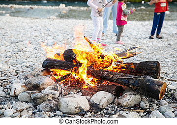 Family enjoying time by the river and self-made campfire...
