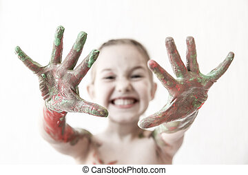 Little girl showing her hands, covered in finger paint