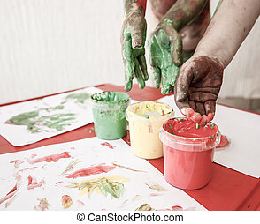 Children dipping fingers in washable finger paints -...