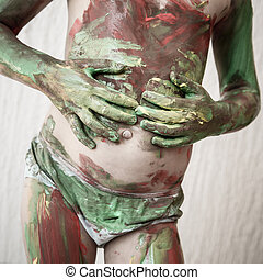 Child body painting himself with finger paints - Little girl...