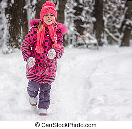 Happy 5 year old girl running on snow-covered park