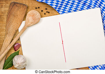 Book with wooden spoons on a bavarian tablecloth