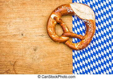 Pretzel with bavarian tablecloth on a wooden background
