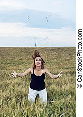 Young woman doing crazy jumps in a wheat field. Natural...