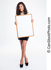 Cheerful busineswoman holding blank board - Full length...