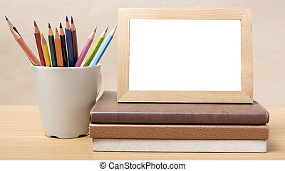 stack of book and photo frame with color pencil
