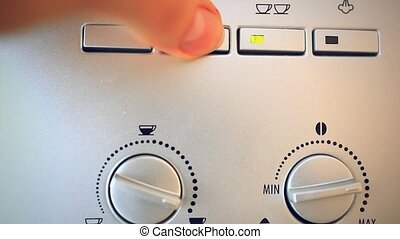 Finger presses the button on the automatic coffee espresso machine.