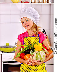 Child cooking at kitchen - Child girl in hat holding...