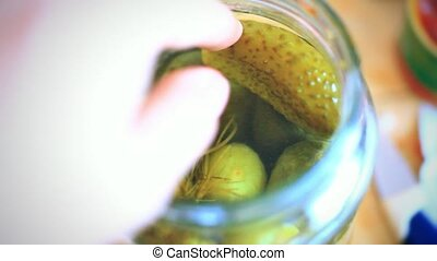 hand gets pickled cucumber from the jar 1920x1080