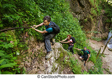 Hikers climbing on a safety cable - Family of hikers...