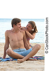 Young couple sitting on the beach - Young woman and man...