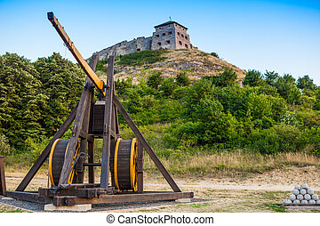 Wooden medieval catapult under old castle