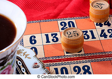 Lotto game on a table with a red cloth, a coffee cup.
