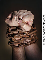 Chained - Hands of a man with a rusty chain around the...
