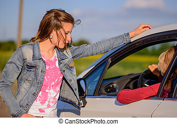 Two women chatting at the roadside with a young woman...