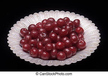 Sour cherry on a silver plate against a black background