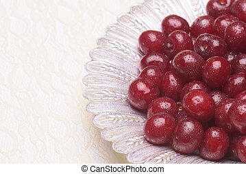 Sour cherry on a silver plate against a light background
