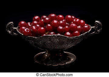 Sour cherry in a silver bowl against a black background