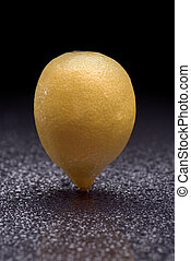Lemon standing - Fresh lemon with water drops standing on a...