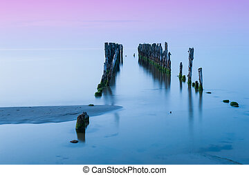 Old pier - Old broken pier at sunset on the coast of the...