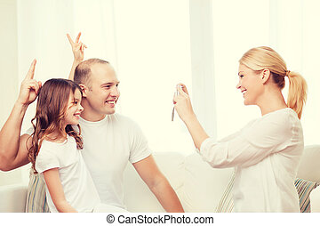 happy mother taking picture of father and daughter - family,...