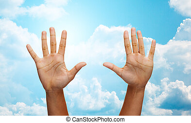 two african hands making high five over blue sky - gesture,...