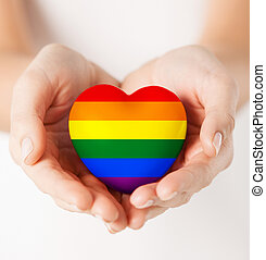 female hands with small rainbow heart - gay pride,...