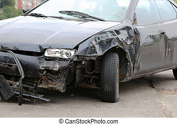 Black crashed car from front on the road