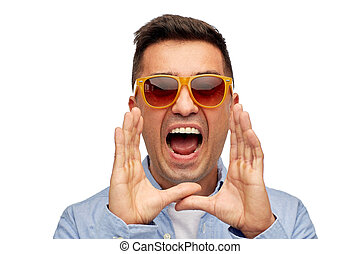 face of angry shouting man in shirt and sunglasses